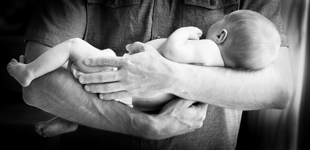 new baby: Cute newborn baby boy being held in his fathers arms against a bare chest in black and white Stock Photo