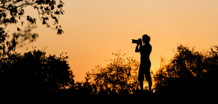botswana: Photographer silhouetted against a golden sunset sky in Africa Stock Photo