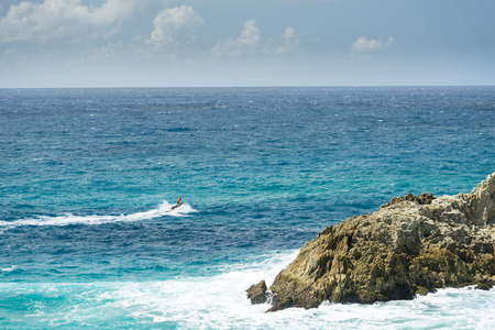 jetski: Surf lifesaver rides a jetski in the ocean around dangerous cliffs in Queensland, Australia