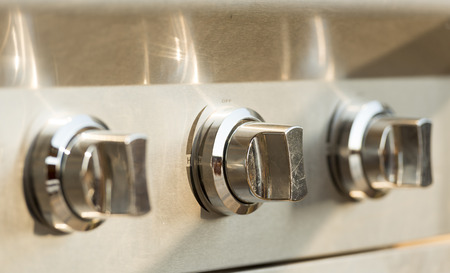 gas burner: Barbecue control dials on a stainless steel gas burner BBQ