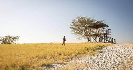 Man geht durch lange Gras in Richtung einer erhöhten Hütte bei Sonnenuntergang während auf Safari in den Makgadikgadi Pans, Botswana, Afrika