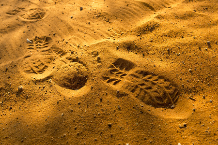 footmark: Footprints in sand at sunset in rich orange colours Stock Photo
