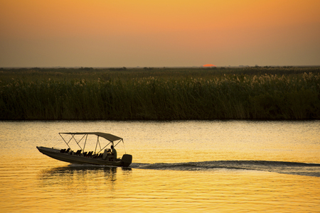 chobe: Silhouetted boat on a river safari on the Chobe River, Botswana, Africa Stock Photo