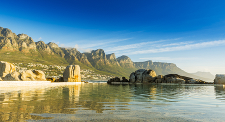 table mountain national park: Camps Bay ocean pool at sunset with city and mountains behind Stock Photo