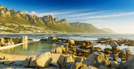western town: Camps Bay ocean pool at sunset with city and mountains behind Stock Photo