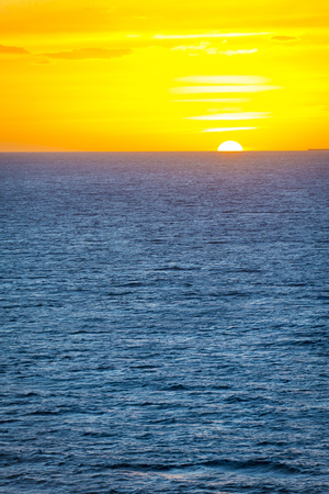 Sunset over the sea with horizon line and gentle ocean waves