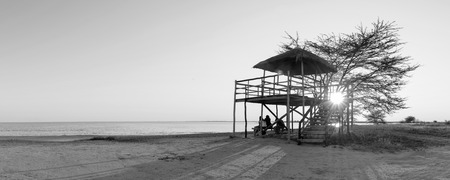 Group of friends sit relaxing at sunset on the beach under a large open air hut in Africa in black and white Stock Photo
