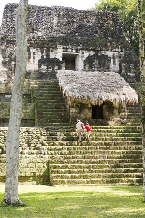 TIKAL, GUATEMALA - NOVEMBER 26: Unidentified people climbed mayan temple ruins at an archealogical site in Tikal National Park on November 26, 2017 in Tikal.