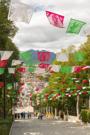 SAN CRISTOBAL, MEXICO - NOVEMBER 28: A view of San Cristobal de las Casas from the steps of the Guadalupe Church with unidentified people under rows of colorful paper flags on November 28, 2016 in San Cristobal. The Guadalupe Church is a popular tourist l
