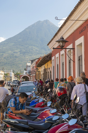 ANTIGUA, GUATEMALA - FEBRUARY 24, 2018: Unidentified people pass by rows of motorbikes lining the streets in Antigua, Guatemala.