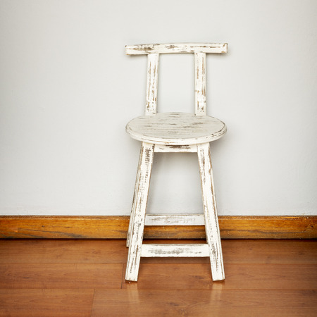 Rustic white wooden stool against a plain wall background