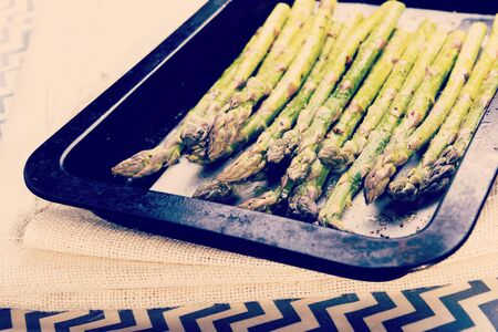 Fresh asparagus spears with salt, pepper and oil ready to be grilled or roasted with retro Instagram style filter effect