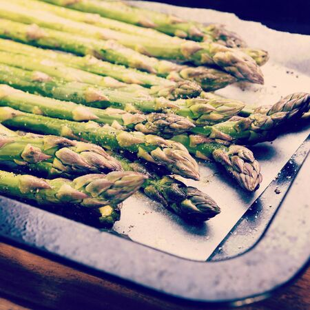 Fresh asparagus spears with salt, pepper and oil ready to be grilled or roasted with retro style filter effect
