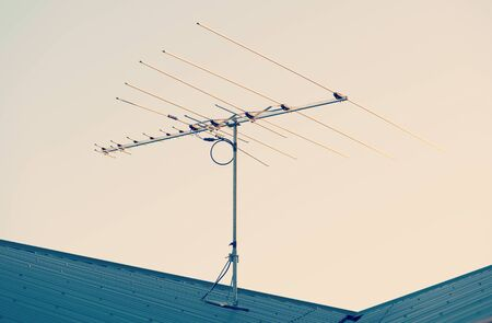 Digital TV aerial or antenna on top of a house with retro style filter effect