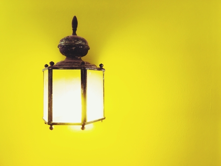 yellow wall: antique indoor lighting with yellow wall background Stock Photo