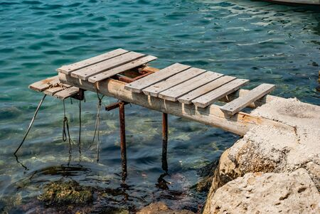 Rusty old pier near the rocky shore of the Adriatic Sea