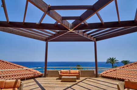 Terrace with wooden pergola and orange sofas