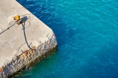 Sea concrete pier with a yellow bollard