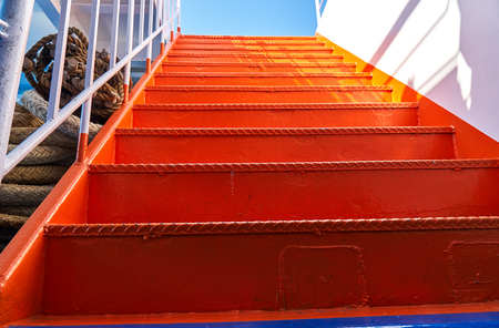 Metal ladder on the ship painted in bright orange color