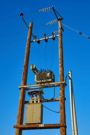 Wooden electric poles with transformers at sunset