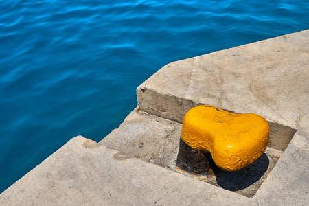 Yellow mooring bollard on a concrete sea pier