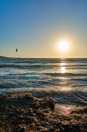 Large waves, sunset and a lonely kitesurfer rolling on the waves