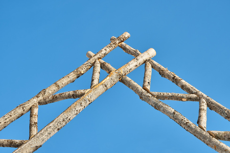 Rustic gate made of logs against the sky