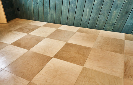 Lacquering wood floors. Plywood floor and a green wall Stockfoto