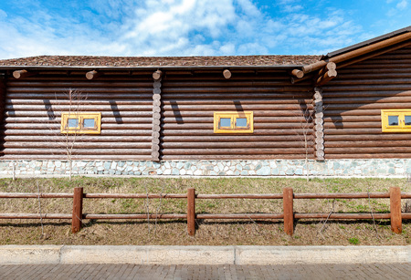 Wooden wall of a log house. Detailed view of one window and two wooden wheels Фото со стока