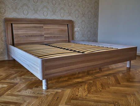 Bed made of solid oak. Bed on the background of patterned wallpaper and wooden flooring