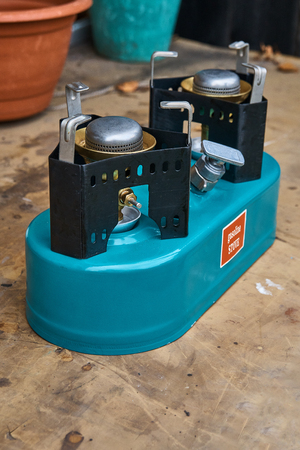 Two-burner primus stove on a dirty table. Primus turquoise