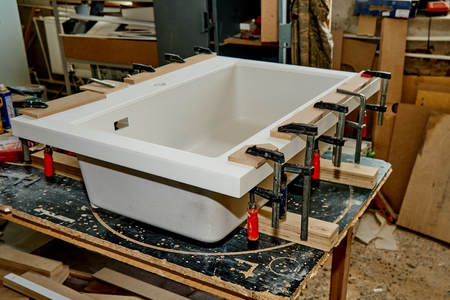 Woodworking and joinery production. Bonding acrylic stone to the sink with clamps. Furniture manufacture