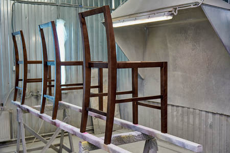 Woodworking and joinery production. Making wooden frame chairs. Painting chairs in the chamber. Furniture manufacture Foto de archivo
