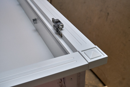White cabinet with hidden hinges and shelf holders. Close-up. Wooden furniture manufacturing process