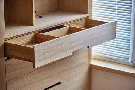 Interior wooden cupboard with empty shelves and opened drawer in daylight. Modern furniture