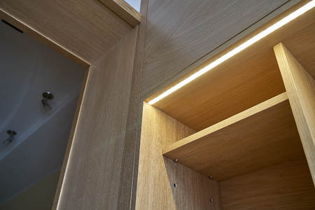 Interior wooden cupboard with empty shelves, drawers and LED lights. Modern furniture 免版税图像