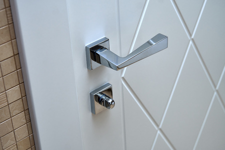 Modern white door with chrome fastener and handle in house bathroom