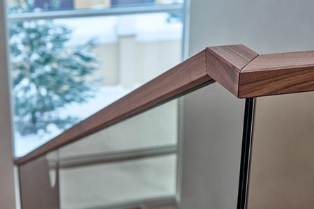Bella ringhiera moderna in vetro per scala in legno con corrimano in legno Archivio Fotografico