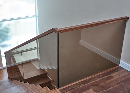 Beautiful modern glass railing for wooden staircase with wooden handrail