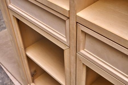 Schöner, professionell gefertigter Holzschrank im Herstellungsprozess in der Werkstatt. Kleiderschrank mit Schubladen. Herstellung von Möbeln. Nahansicht Standard-Bild