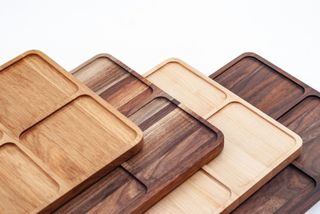 Row arrangement of carved wooden panels of different colors and timber on white background