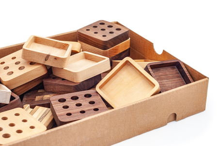 Chaotic pile of various lumber trays and carved details made of different wood species in carton box
