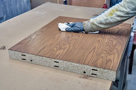 Worker stained veneer panels in painting chamber. Production of wood furniture. Furniture manufacture. Close-up