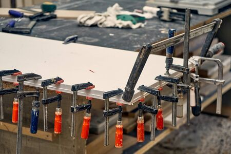 Gluing and clamping table top of acrylic stone in workshop. Furniture manufacture. Close-up Imagens
