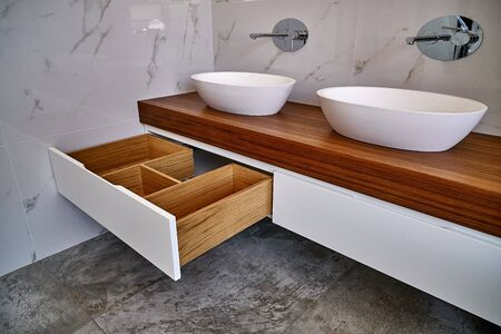 Ceramic round sinks placed on teak tabletop in luxury water closet with gray and white marble walls