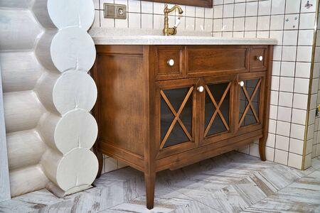 Eleganter Badezimmer-Waschtisch mit Acryl-Arbeitsplatte in der Nähe der gefliesten Wand in einem luxuriösen WC. Landhausstil. Details Möbel