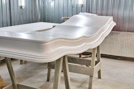 Curved crown molding of a classic wardrobe after finishing painting in painting chamber. Furniture manufacture. Close-up