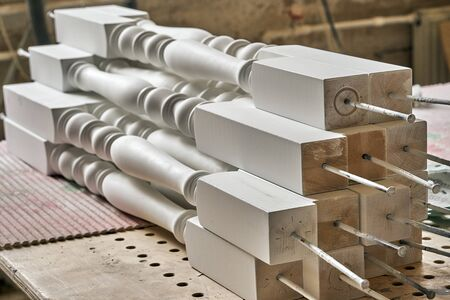Beautiful professionally made solid wood balusters in process of production in workshop. Furniture manufacture. Close-up