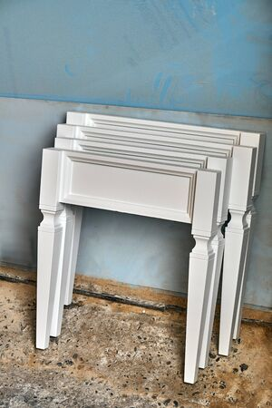 Elements of a white nightstand in process of production in workshop. Wooden furniture manufacturing process. Close-up