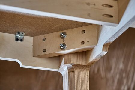 Beautiful professionally made wood writing desk in process of production in workshop. Furniture manufacture. Close-up